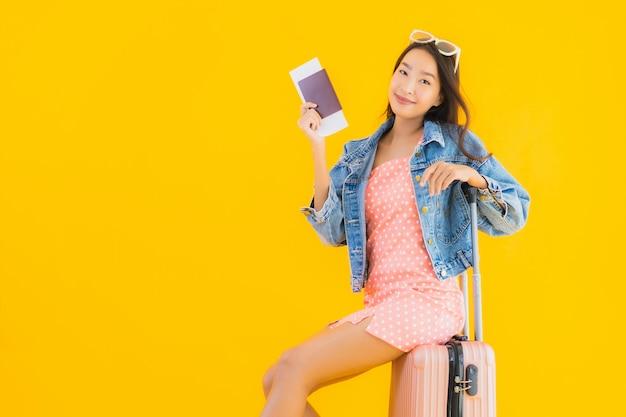 Retrato hermosa joven asiática con bolsa de viaje de equipaje con pasaporte y boleto de embarque