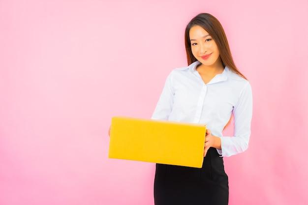 Retrato hermosa joven asiática con caja de embalaje lista para enviar en la pared de color rosa