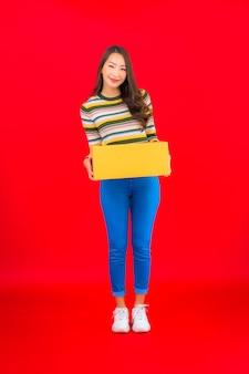 Retrato hermosa joven asiática con caja de paquetería en pared roja aislada