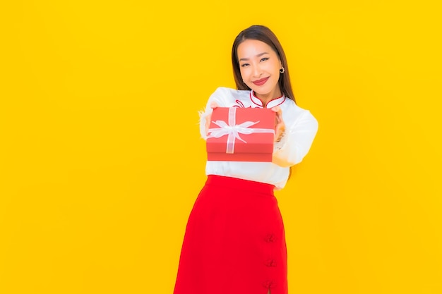 Retrato hermosa joven asiática con caja de regalo roja sobre amarillo