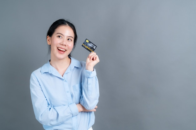 Retrato de una hermosa joven asiática en camisa azul que muestra la tarjeta de crédito con espacio de copia