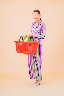 Retrato hermosa joven asiática con canasta de supermercado en color
