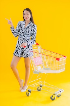 Retrato hermosa joven asiática con carrito de compras para compras en amarillo