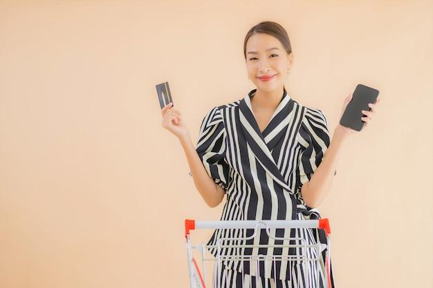 Retrato hermosa joven asiática con carrito de compras