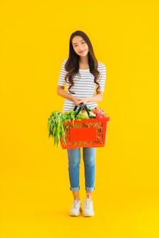 Retrato hermosa joven asiática con carrito de supermercado del supermercado en el centro comercial