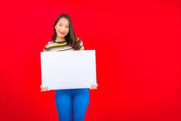 Retrato hermosa joven asiática con cartelera vacía blanca en la pared roja