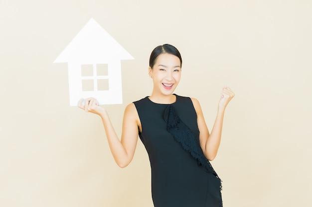 Retrato hermosa joven asiática con casa o cartel de papel casero en la pared de color