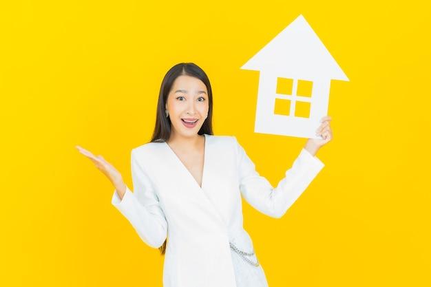 Retrato hermosa joven asiática con casa o cartel de papel casero