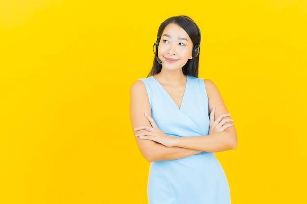 Retrato hermosa joven asiática con centro de servicio de atención al cliente de call center en la pared de color amarillo