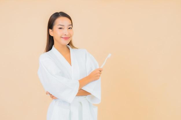 Retrato hermosa joven asiática con cepillo de dientes en beige
