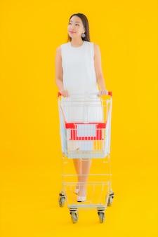 Retrato hermosa joven asiática con cesta de la compra para ir de compras en el supermercado