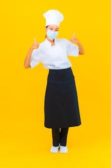 Retrato hermosa joven asiática chef usar máscara para proteger covid19 o coronavirus sobre fondo amarillo aislado