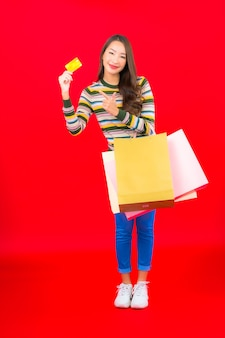 Retrato hermosa joven asiática con colorido bolso de compras y tarjeta de crédito en la pared roja