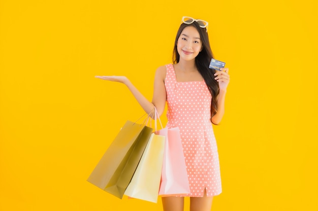 Retrato hermosa joven asiática con colorido bolso de compras con tarjeta de crédito