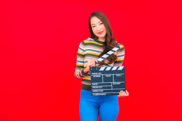 Retrato hermosa joven asiática con corte de pizarra de película en pared roja aislada