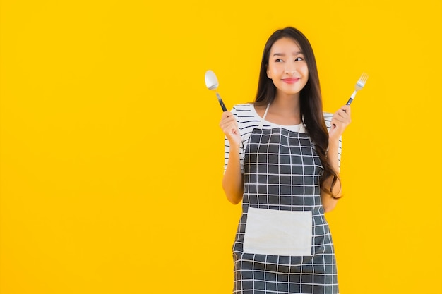 Retrato hermosa joven asiática con cuchara y tenedor