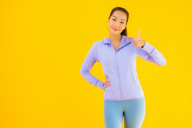 Retrato hermosa joven asiática deporte mujer lista para hacer ejercicio en amarillo