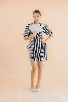 Retrato hermosa joven asiática con dinero en efectivo y dinero