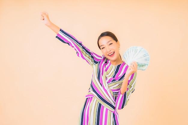 Retrato hermosa joven asiática con dinero en efectivo o dinero y teléfono móvil inteligente en color