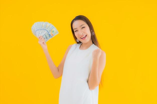 Retrato hermosa joven asiática con dinero en efectivo