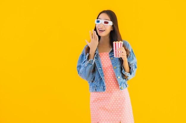 Retrato hermosa joven asiática disfruta feliz con palomitas de maíz y mira la película