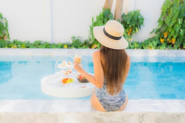 Retrato hermosa joven asiática disfrutar con té de la tarde o desayuno flotando en la piscina