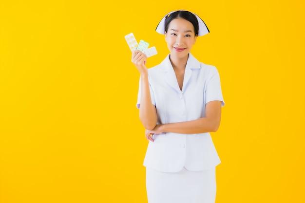 Retrato hermosa joven asiática enfermera tailandesa con píldora o droga