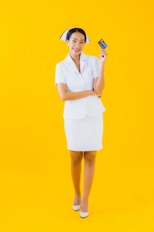 Retrato hermosa joven asiática enfermera tailandesa con tarjeta de crédito