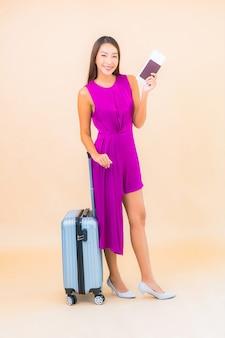Retrato hermosa joven asiática con equipaje y billete de avión sobre fondo de color