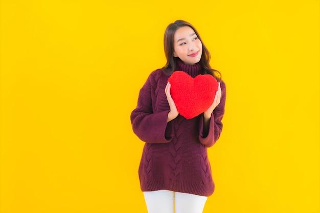 Retrato hermosa joven asiática con forma de almohada de corazón