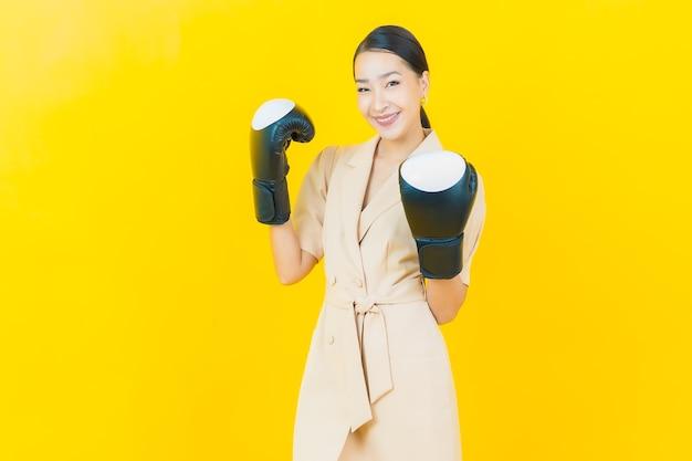 Retrato hermosa joven asiática con guante de boxeo en la pared de color