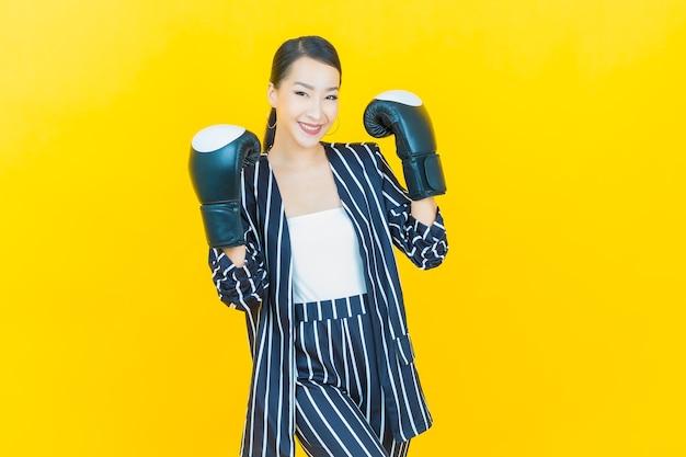 Retrato hermosa joven asiática con guante de boxeo sobre fondo de color