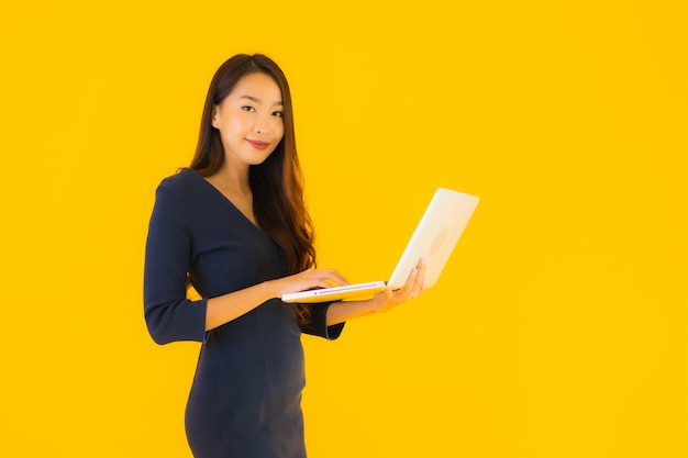 Retrato hermosa joven asiática con laptop