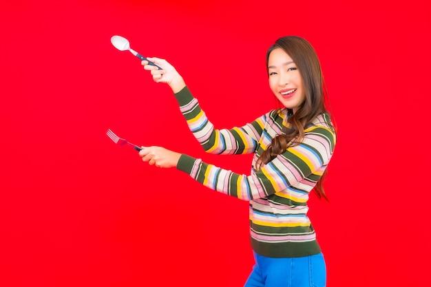 Retrato hermosa joven asiática lista para comer con cuchara y tenedor en la pared roja