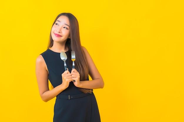 Retrato hermosa joven asiática lista para comer con tenedor y cuchara sobre fondo amarillo