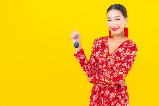Retrato hermosa joven asiática con llave de coche en pared amarilla
