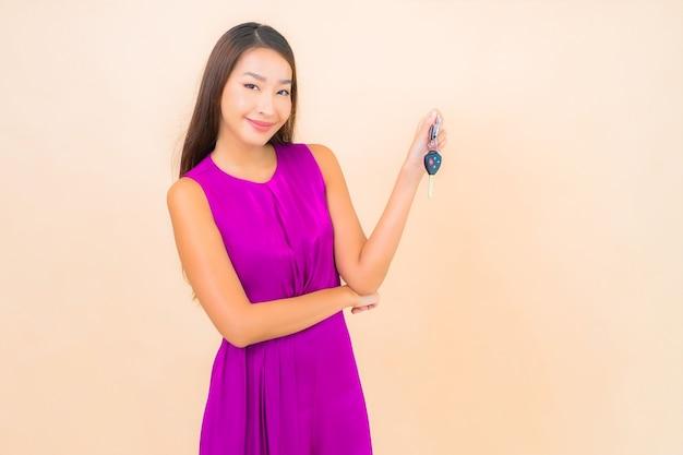 Retrato hermosa joven asiática con llave de coche sobre fondo de color aislado