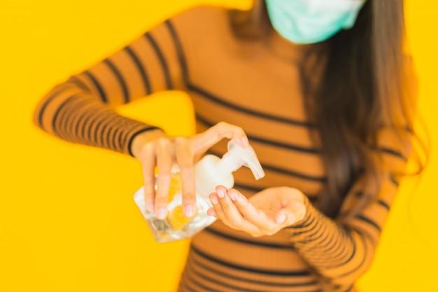 Retrato hermosa joven asiática con máscara de aerosol de alcohol y botella de gel en la mano para proteger de coronavirus o covid19