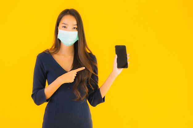 Retrato hermosa joven asiática con máscara y teléfono
