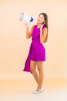 Retrato hermosa joven asiática con megáfono sobre fondo de color aislado