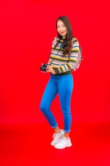 Retrato hermosa joven asiática con mochila de cámara y mapa en pared roja aislada