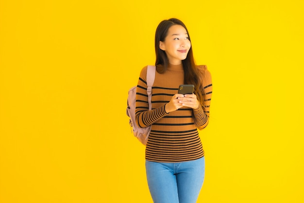 Retrato hermosa joven asiática con mochila utiliza smartphone
