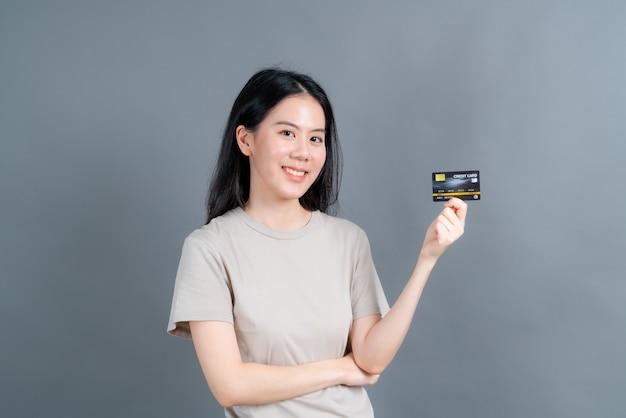 Retrato de una hermosa joven asiática mostrando tarjeta de crédito con espacio de copia