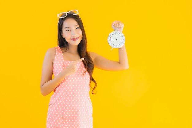 Retrato hermosa joven asiática mostrar alarma o reloj