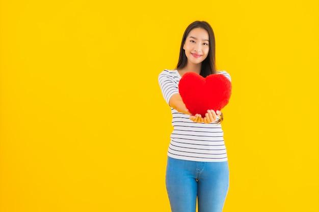Retrato hermosa joven asiática mostrar almohada corazón