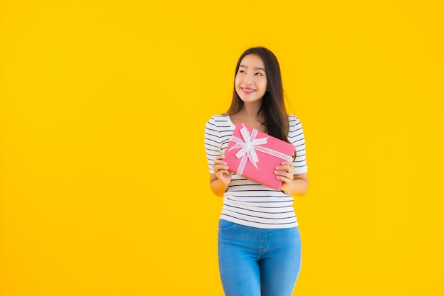 Retrato hermosa joven asiática mostrar caja de regalo roja