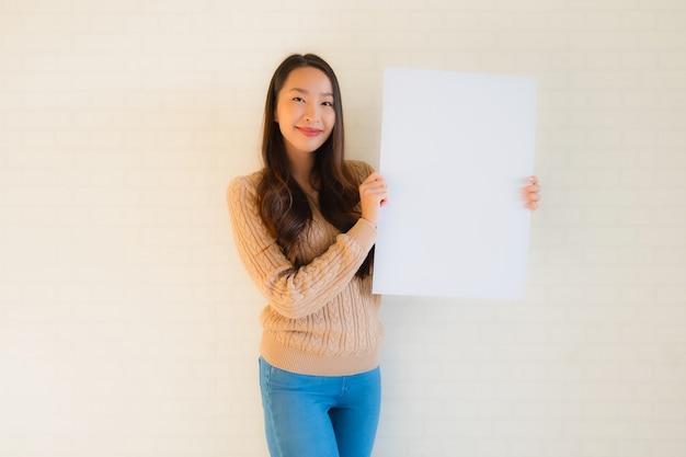 Retrato hermosa joven asiática mostrar pizarra en blanco de papel blanco