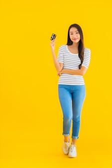 Retrato hermosa joven asiática mostrar tarjeta de crédito