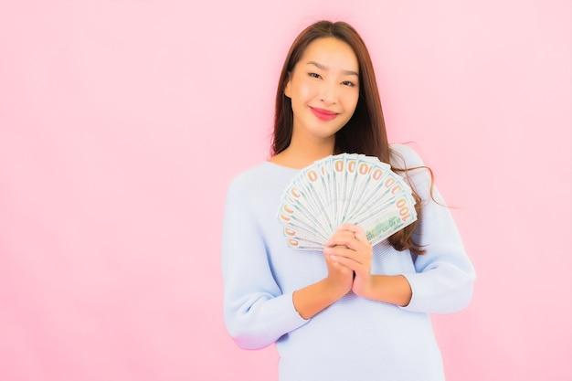 Retrato hermosa joven asiática con mucho dinero en efectivo y dinero en la pared de color rosa