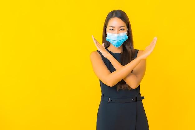 Retrato hermosa joven asiática mujer de negocios usar máscara para proteger covid19 sobre fondo amarillo